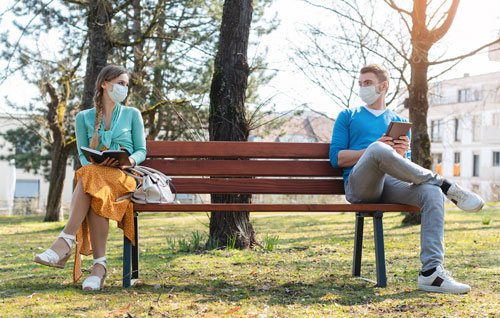 Social distancing: young man and woman, both with face coverings, sitting at opposite ends of a long park bench